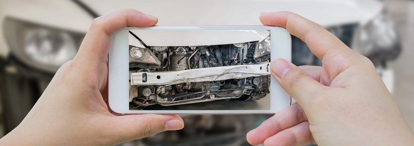 female hold mobile smartphone photographing car accident for insurance